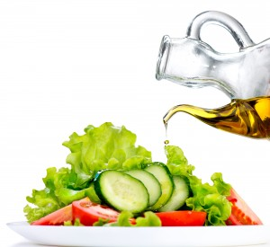 Healthy vegetable salad with olive oil dressing over white